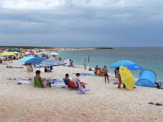 FET_Sardinien_rejsereportage_På-kvartsstemns-stranden-Is-Arutas-skal-publikum-skylle-fødderne-før-den-forlader-stranden,-for-at-det-fine-'smykke-stens'-sand-ikke-skal-forsvinde.